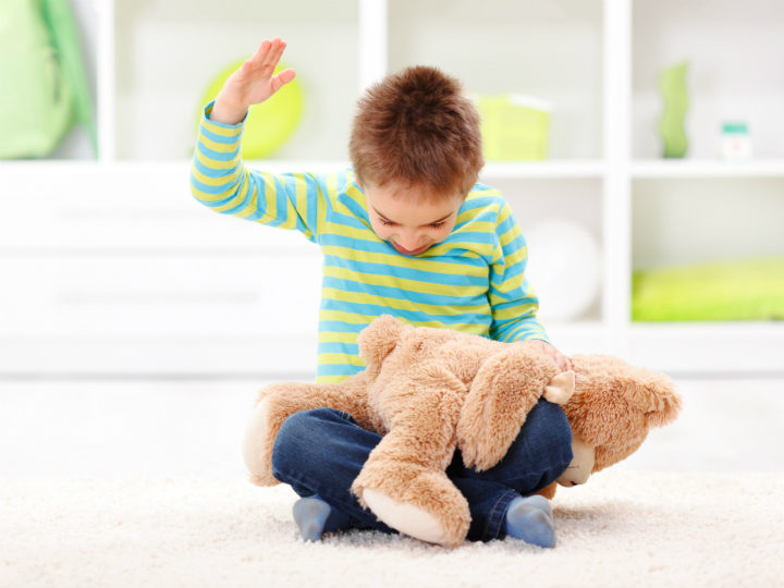 boy hitting stuffed bear