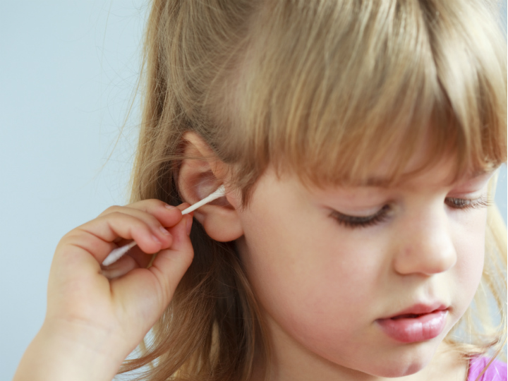 child using cotton swab in ears