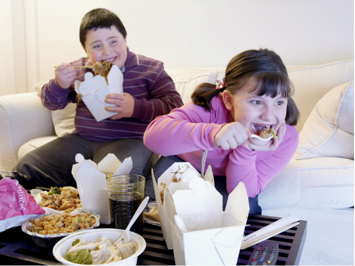 kids eating dinner in front of TV