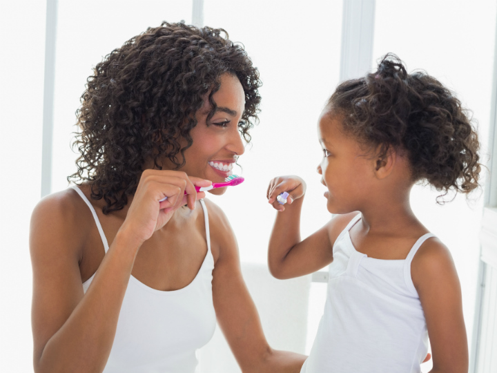 mom teaching young girl to brush teeth