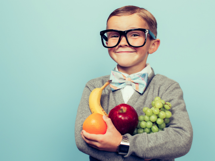 young boy with glasses holding fruits and veggies