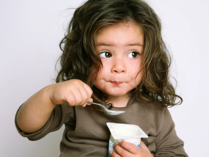 young child eating yogurt