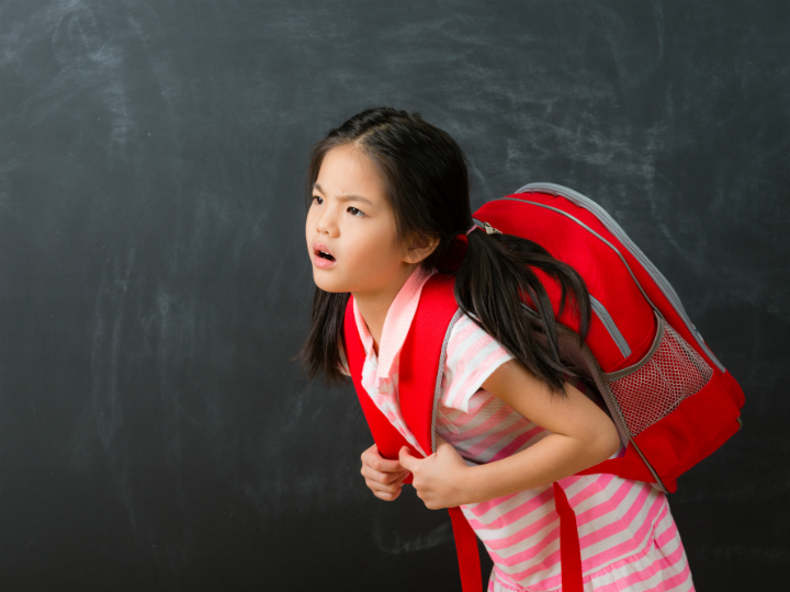 young girl with heavy backpack
